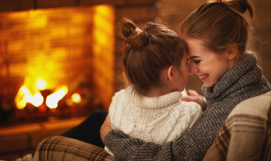 family mother and child daughter hugs and laughing on winter evening by fireplace