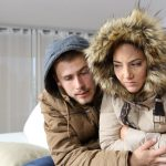 Cold home with an angry couple warmly clothed hugging sitting on a sofa in the living room