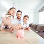 Mother, father, daughter and son sit around the kitchen table and put a coin in a pink piggy bank