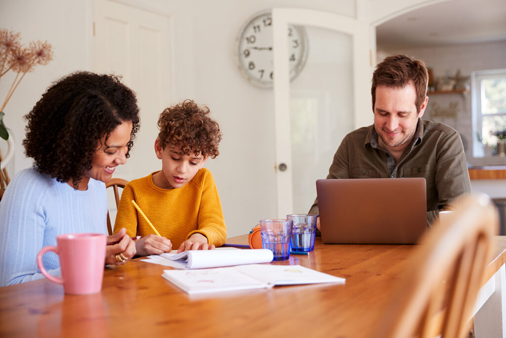 Father Works On Laptop As Mother Helps Son With Homework