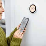 .woman setting thermostat with phone
